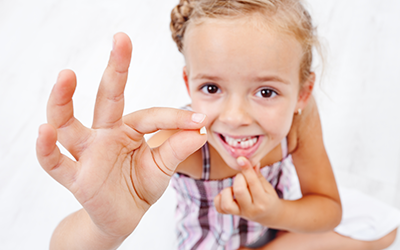 Child with tooth in hand