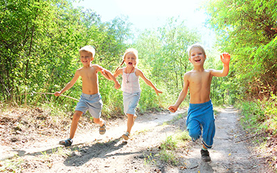 Three kids running outdoors